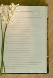 铃兰分支在笔记本的 免版税库存照片