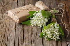 铃兰花束与礼物的在木土气b 库存照片
