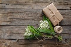 铃兰花束与礼物的在木土气b 免版税库存照片