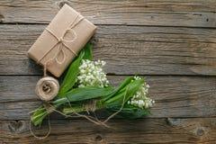 铃兰花束与礼物的在木土气b 图库摄影