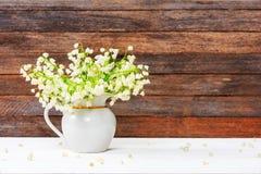 铃兰花束在一张白色木桌上的一个水罐开花在减速火箭的难看的东西墙壁背景 免版税库存照片