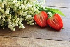 铃兰,在木背景的铃兰春天花束  草莓 库存照片