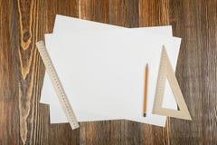 铅笔、三角和简单的厘米统治者在白皮书在顶视图 免版税库存照片