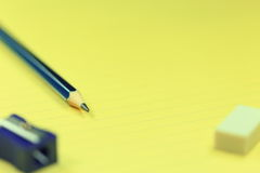 铅笔、磨削器、橡皮擦和纸 免版税库存照片