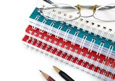 铅笔、笔、笔记本和玻璃 免版税库存照片