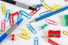 铅笔、笔、纸夹、磨削器和图钉在白色桌面上 免版税库存图片