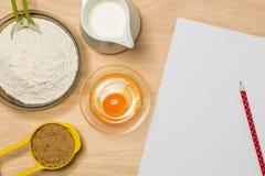 铅笔、纸、面粉、鸡蛋、牛奶和糖 免版税库存照片