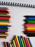 铅笔、蜡笔和标志,上色在笔记本旁边的学校文章 库存图片