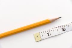 铅笔和两英寸测量的磁带 免版税库存照片
