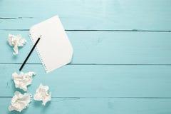 铅笔和倒空在蓝色木桌背景的白皮书 免版税库存图片