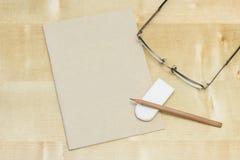 铅笔和橡胶在笔记本与草 免版税库存图片