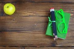 铅笔和玻璃、一本书和一个苹果在木背景 免版税库存照片