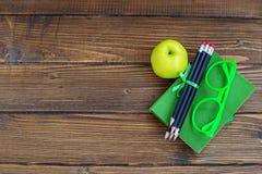 铅笔和玻璃、一本书和一棵美味苹果在木ba 库存照片