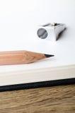 铅笔和磨削器在空白的写生簿页 免版税库存图片