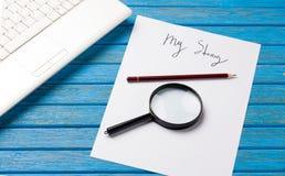 铅笔和纸与我的故事在笔记本附近措辞 免版税库存照片