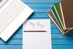 铅笔和纸与我的故事在笔记本附近措辞 库存图片