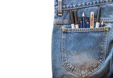 铅笔和魔术笔和老切削刀在口袋蓝色牛仔裤在白色隔绝了背景 免版税库存图片