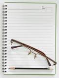 铅笔和玻璃在纸笔记 库存照片