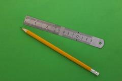 铅笔和统治者在绿色背景 免版税库存照片