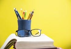 铅笔在笔匣和玻璃上色在一本书在图书馆黄色教育概念回到学校/蜡笔 免版税图库摄影