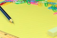 铅笔,统治者,橡皮擦,在纸的纸夹 免版税库存图片