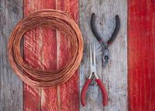铜丝和钳子在木背景 免版税库存图片
