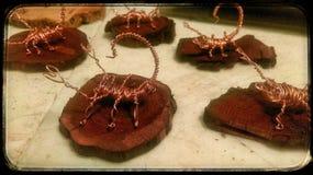 铜丝在被弄脏的豆科灌木登上的蝎子雕塑 库存图片