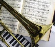 黄铜伸缩喇叭和古典音乐放置了在合成器键盘 免版税库存图片
