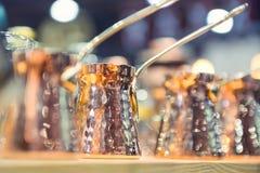 铜土耳其人行烹调的咖啡在厨房架子 选择聚焦 背景bokeh音乐注意主题 免版税库存图片