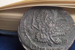 铜币1785在有胳膊特写镜头的俄罗斯在书页下 免版税库存图片