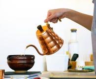 从铜瓶子的倾吐的水到大棕色黏土杯子 免版税库存图片