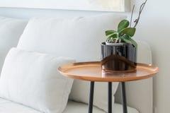 铜盘子边桌,与黑腿,在一个白色蒲团长沙发旁边,聚焦在距离,与兰花盆的植物 免版税库存照片