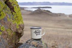 铝上釉了一个旅客的杯子用在一座青苔隐蔽的山的热的茶在贝加尔湖美丽如画的背景  库存照片