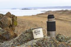 铝在早期的春天上釉了阵营杯子用茶和在贝加尔湖石岸的一个金属热水瓶  库存图片