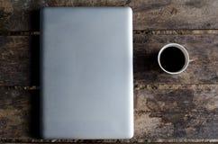 铝笔记本(膝上型计算机)有杯子的在木桌上的热的咖啡 库存照片