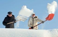 铲起在屋顶的人们雪 免版税库存图片
