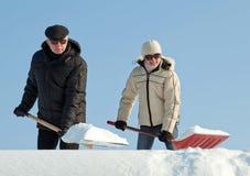 铲起在屋顶的人们雪 免版税图库摄影