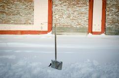 铲起在砖墙的背景的随风飘飞的雪 库存图片
