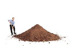 铲起大堆土的快乐的年轻人 免版税库存照片