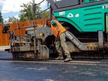 铲起热的沥青的修路工作者 免版税库存照片