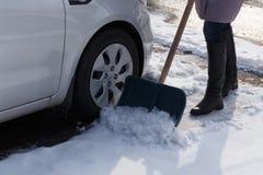 铲起这里停车场的妇女在冬天暴风雪以后 图库摄影