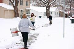 铲起降雪的大量邻居 免版税图库摄影