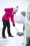 铲起雪的妇女在汽车附近 免版税库存照片
