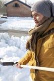铲起雪的年轻人在农场附近 图库摄影