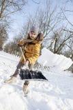 铲起雪的年轻人在小木头附近 免版税库存照片