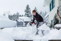 铲起雪的年轻男孩 库存照片
