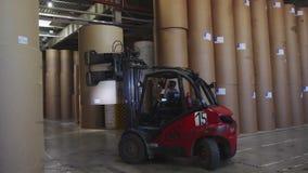 铲车装载者在仓库投入在堆上的纸板卷 股票视频