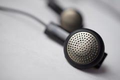 银和黑穿孔的耳机(耳朵芽)的宏观细节有缆绳的 免版税库存图片