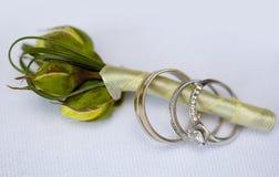 银婚圆环和定婚戒指与出价的金刚石在新郎钮扣眼上插的花有丝绸丝带的 图库摄影