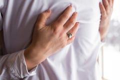 银婚圆环和定婚戒指与金刚石在手边妇女 拥抱衣服的新娘新郎 库存图片